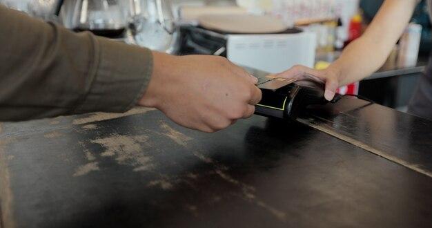 Chiudere la paga del cliente per il caffè da asporto utilizzando il pagamento senza contatto con carta di credito spendendo denaro in un bar con servizio di transazione digitale.