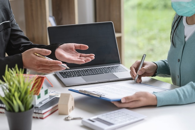 Primo piano del cliente che firma il contratto un accordo per vendere una casa con un agente in ufficio.
