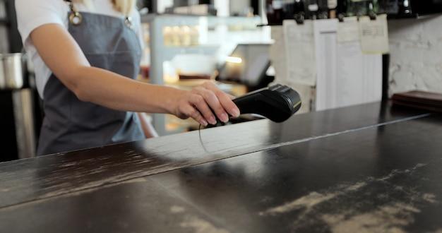 Primo piano del cliente per un caffè da asporto che paga con uno smartwatch senza contatto nfc con una macchina per carte. pagare in un bar con uno smartwatch. tecnologia.