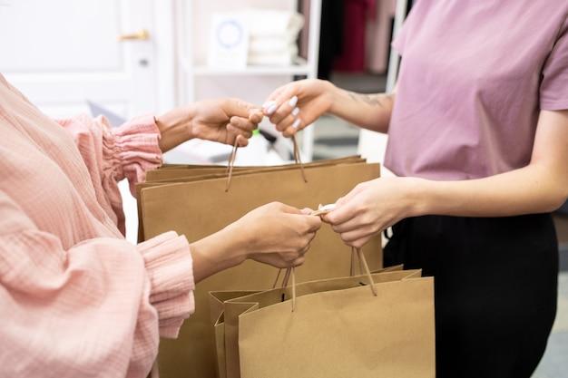 Primo piano del cliente che prende le borse della spesa di carta dalla commessa nel negozio