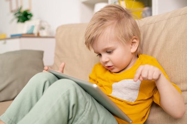 Primo piano del ragazzo carino seduto sul divano e parlando con il genitore tramite l'app di telecomunicazione sul tablet in soggiorno