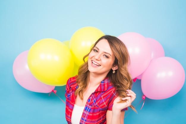 Primo piano di una ragazza bruna carina in piedi in uno studio, che sorride ampiamente e gioca con palloncini gialli e rosa. si sta divertendo.
