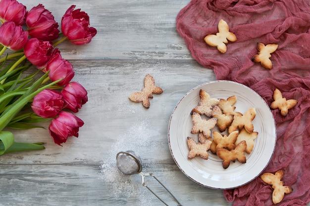 Primo piano dei biscotti svegli della farfalla sul piatto e sui tulipani rossi beautful