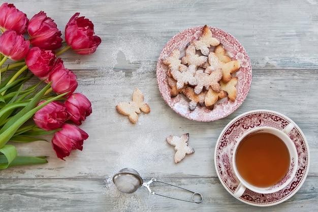 Close-up di un simpatico farfalla cookie su un piatto, tazza di tè e tulipani rossi.