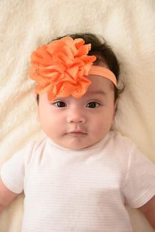 Primo piano di carino piccolo bambino asiatico che indossa la testa di fiori d'arancio