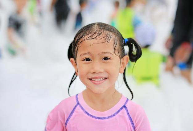 Ragazza asiatica sveglia sveglia del bambino del primo piano che sorride divertendosi nel partito della schiuma allo stagno all'aperto.