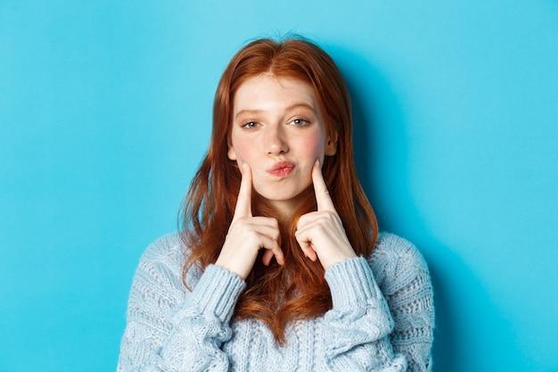 Close-up di carina ragazza rossa in maglione, labbra pucker e puntare le dita sulle guance, colpendo fossette, in piedi su sfondo blu