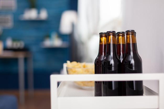 Chiuda in su della bottiglia di birra scura in appartamento elegante. soggiorno moderno senza nessuno con mobili e pareti blu, splendidamente decorato. arredamento abbastanza semplice dell'appartamento. elegante decorazione retrò, perché