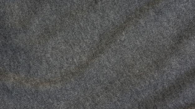 Primo piano di tessuto morbido grigio scuro per uno sfondo.