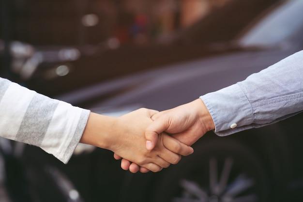 Chiuda in su del concessionario che dà la chiave al nuovo proprietario e si stringono la mano nel salone dell'auto o nel salone