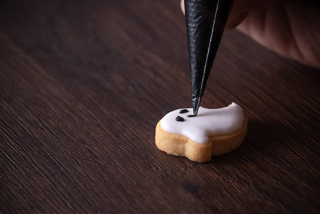 Primo piano di decorare biscotti di panpepato fantasma carino halloween con glassa glassa crema topping bag.