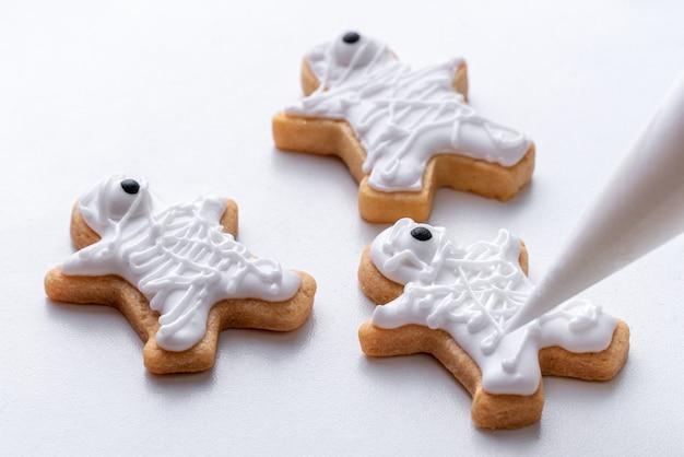 Close up di decorare graziosi biscotti di panpepato di halloween con glassa glassa crema topping bag.