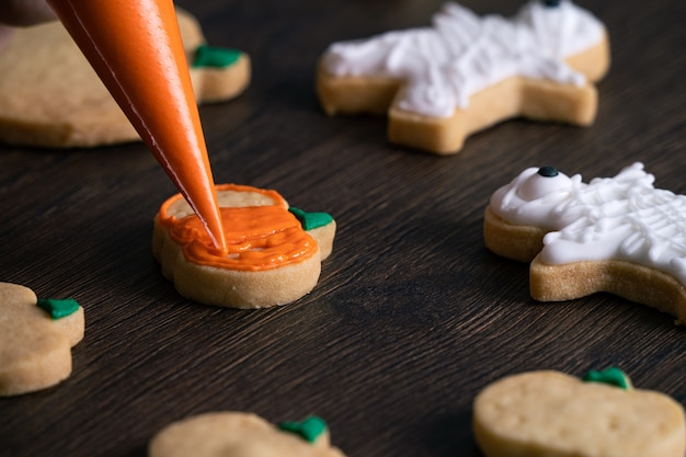Primo piano di decorare i simpatici biscotti di panpepato di zucca di halloween con glassa di crema topping bag.