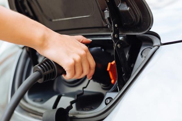 Il primo piano di mani femminili delicate e ordinate che caricano l'auto inserendo una bocchetta di alimentazione nell'unità di potenza dell'auto