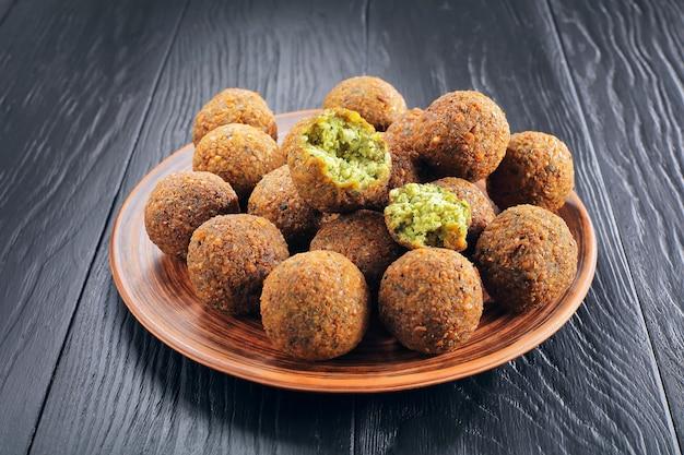 Primo piano di deliziose palline di falafel e uno è rotto in pezzi su un piatto di argilla sul tavolo di legno nero