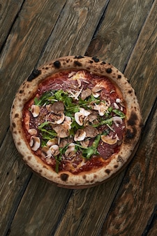 Primo piano su una deliziosa pizza piccola appena sfornata con funghi e rucola al formaggio fuso.