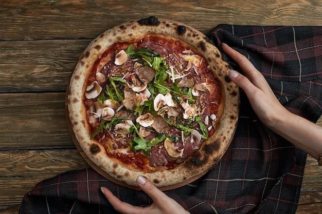 Primo piano su una deliziosa pizza piccola appena sfornata con funghi e basilico al formaggio fuso.