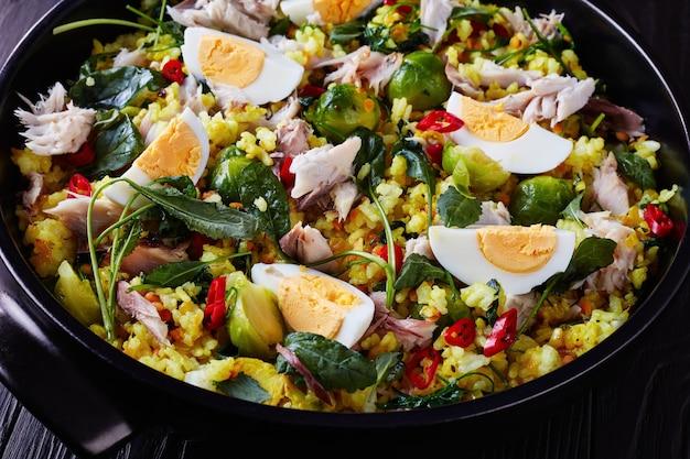 Close-up di deliziosi kedgeree con fiocchi di pesce affumicato, uova sode, riso, cavoli, cavoletti di bruxelles, spezie ed erbe aromatiche in un forno olandese su un tavolo di legno nero, vista da sopra,