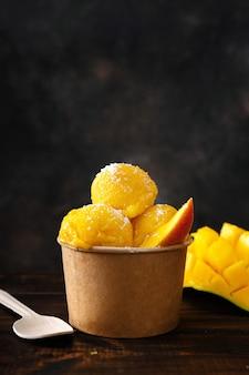 Primo piano di delizioso sorbetto al mango in un bicchiere di carta eco friendly