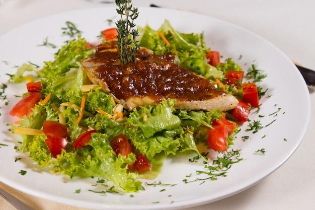 Primo piano delizioso piatto di carne su lattuga e pomodori in una bella placcatura.