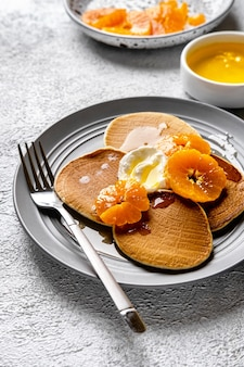 Close-up deliziose frittelle con mandarini e miele o sciroppo d'acero per colazione su sfondo chiaro.