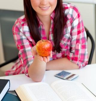 Primo piano di una donna caucasica contentissima che tiene una mela che si siede nella cucina
