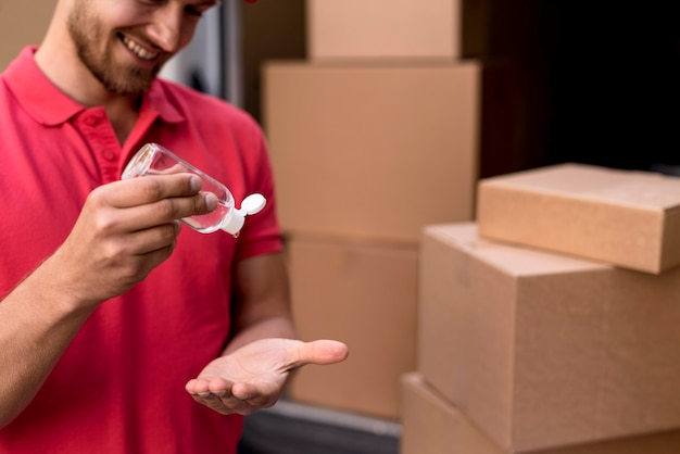 Maschio di consegna del primo piano che usando disinfettante per le mani