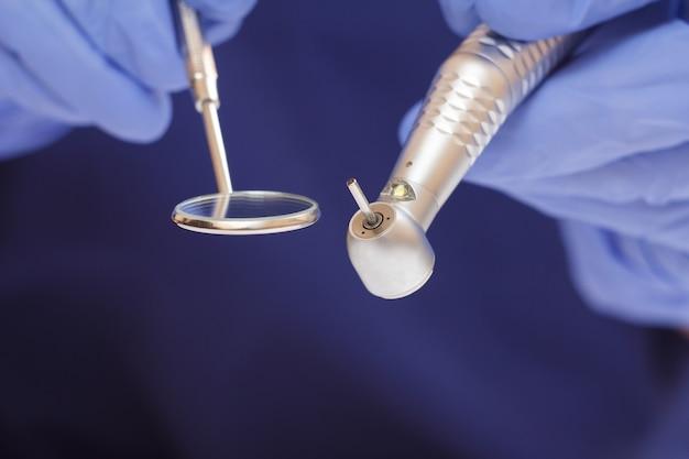 Primo piano delle mani del dentista in guanti in lattice con specchio per la bocca e manipolo dentale ad alta velocità su sfondo sfocato. concetto di strumenti medici. profondità di campo ridotta.