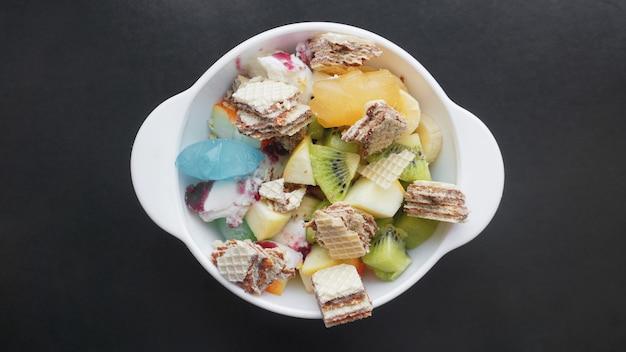 Primo piano deserto con frutta fresca e gelato. frutta mista con cialda e ghiaccio alla frutta su superficie nera