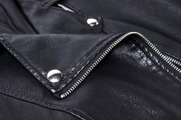 Dettaglio del primo piano della giacca di pelle nera con rivetti e elementi di fissaggio.