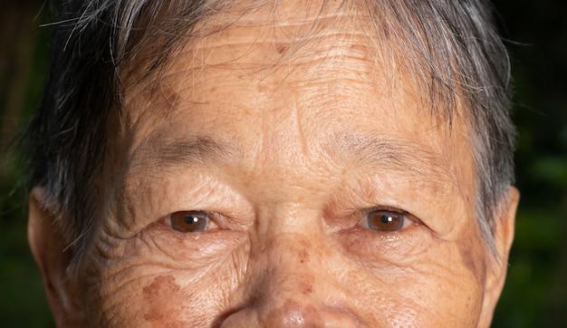 Dettaglio del primo piano degli occhi della donna asiatica anziana.