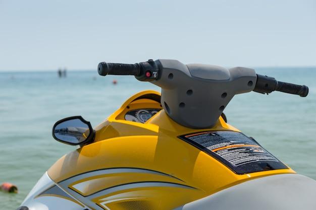 Close up dettaglio del manubrio e specchio su un giallo brillante jet ski contro un oceano calmo in una calda giornata estiva