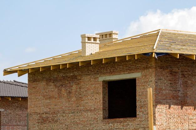 Dettaglio del primo piano del tetto di legno di nuova casa con mattoni a vista con due camini bianchi in costruzione. struttura in legno di materiali naturali contro il cielo luminoso. concetto di costruzione e ricostruzione professionale.