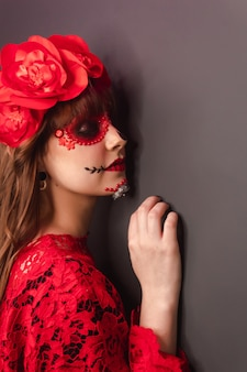 Primo piano dei dettagli del profilo di una ragazza con il trucco dia de los muertos.