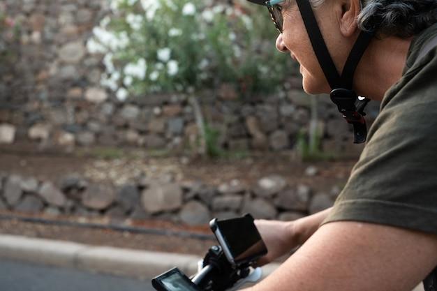 Primo piano sui dispositivi di e-bike. persone che si godono la bicicletta con il cellulare che registra la strada. luce del tramonto. fiori e pietre sullo sfondo