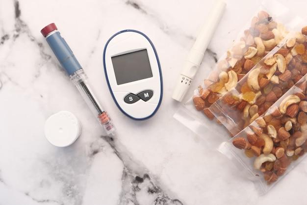 Chiuda in su dell'insulina degli strumenti di misurazione del diabete e del dado misto sul tavolo