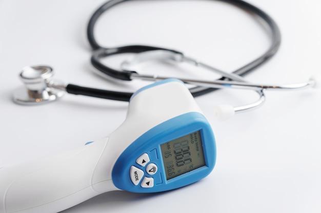 Primo piano del termometro e dello stetoscopio digitali a infrarossi