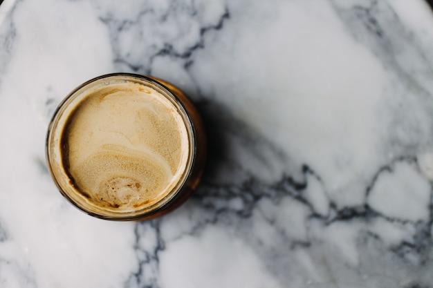 Chiuda in su del caffè latte sporco con struttura in marmo sul caffè e sul tavolo.
