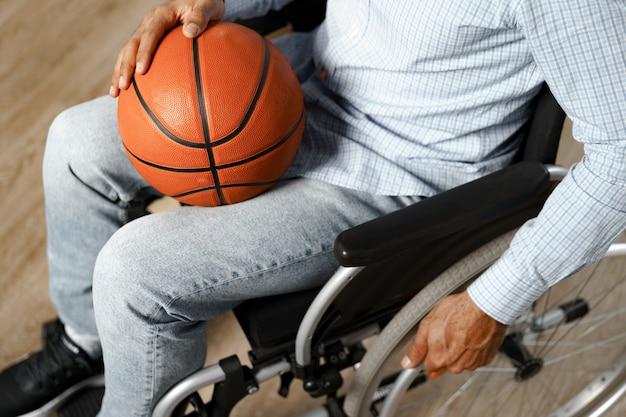 Primo piano di un uomo disabile seduto su una sedia a rotelle e che tiene in mano una palla da basket