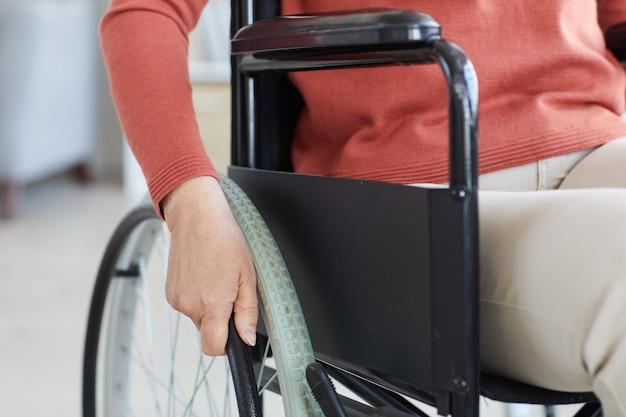 Primo piano della donna senior disabile che si siede in sedia a rotelle e si muove attraverso la stanza