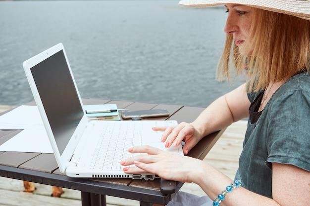 Il primo piano di una donna disabile utilizza un computer portatile all'aperto. lavoro a distanza, concetto di apprendimento.