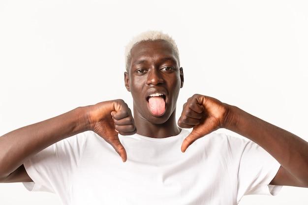 Primo piano del maschio biondo afroamericano deluso che mostra il pollice in giù e la lingua del bastone dalla delusione, antipatia e giudicare qualcosa di brutto