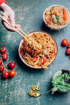 Primo piano su un piatto di spaghetti cinesi tagliatelle avvolgimento mano femminile su bastoni accanto al basilico pomodori sul verde