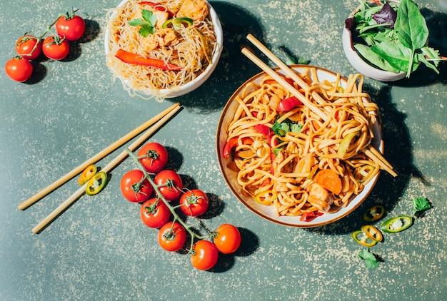 Primo piano di un piatto di spaghetti cinesi con carne e verdure in piatti e bacchette cinesi su una superficie verde