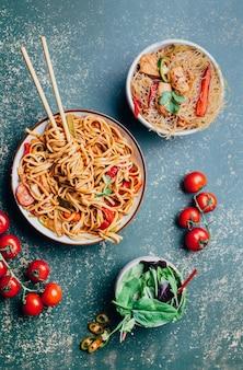 Primo piano di un piatto di spaghetti cinesi con carne e verdure in piatti e bacchette cinesi su un verde