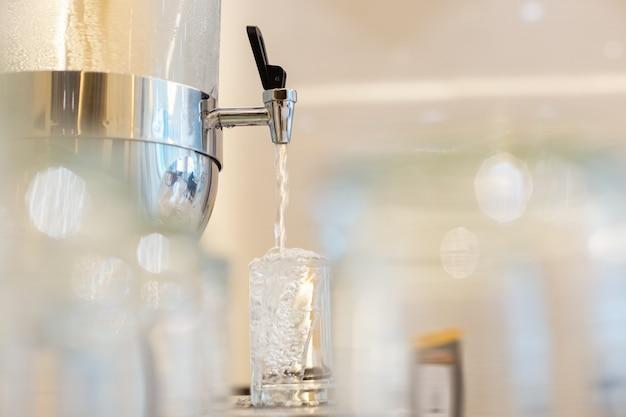 Close up dispenser cooler bere acqua fredda fresca. goccioline d'acqua in un bicchiere d'acqua. sfocatura in primo piano.