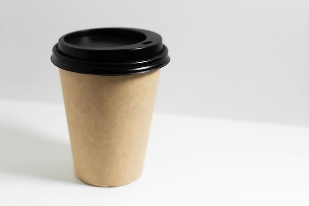 Primo piano del bicchiere di carta usa e getta per il caffè da asporto, con coperchio nero, isolato su bianco.
