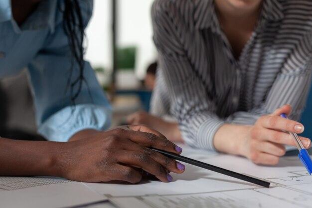 Primo piano di diverse mani di donne architetto che lavorano su piani di progetto alla scrivania ingegnere professionista t...