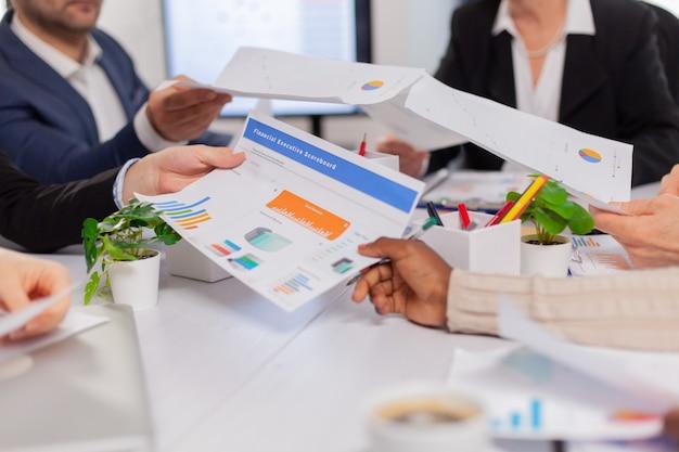 Primo piano di diversi colleghi di aziende startup che si incontrano in un posto di lavoro professionale, brifing e condivisione di idee sulla strategia finanziaria financial