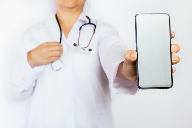 Primo piano della mano del medico con il telefono cellulare bianco.